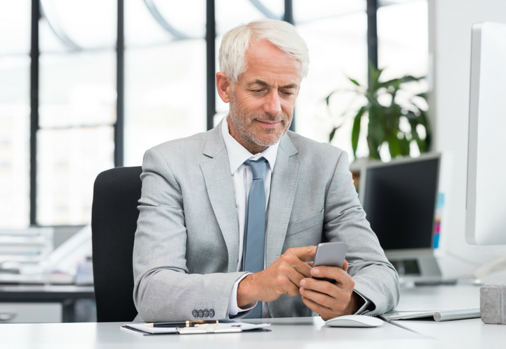 older corporate executive type gentleman with gray hair and a stubble beard smiling and scrolling through his gray phone in front of his desk