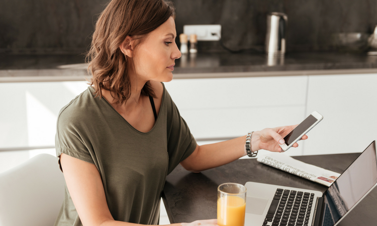 Woman in her 30s looking mildly at her phone in her right hand. She has a glass of orange juice in the other and a laptop in front of her. She's wearing a light, informal olive shirt.