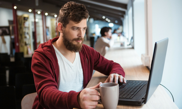 younger man with a beard wearing a white tshirt and maroon hoodie with a coffee cup in one hand and typing on a laptop computer in another, looks like he's in a coffee shop