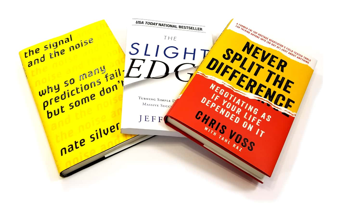 three books splayed from left to right: the signal and the noise by night silver, the slight edge by jeff olson, never split the difference by chris voss