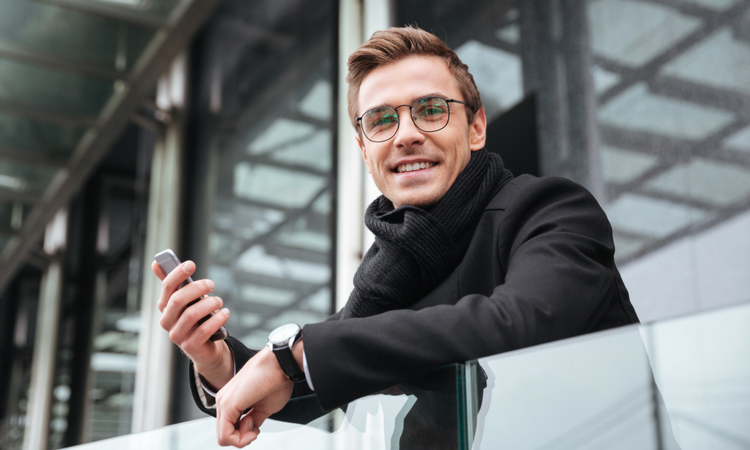 Younger guy in glasses wearing a black jacket, leaning over a rail and looking away from his phone to half smile.