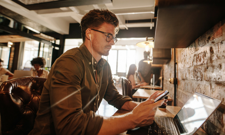 younger man in glasses at a coffee shop looking at his phone in front of a laptop