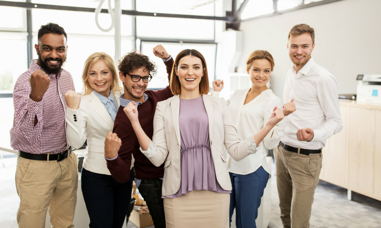group of six younger employees in office with a jubilant, celebratory pose