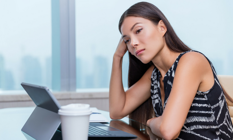 disappointed woman sitting in front of laptop, looking to the left pensively