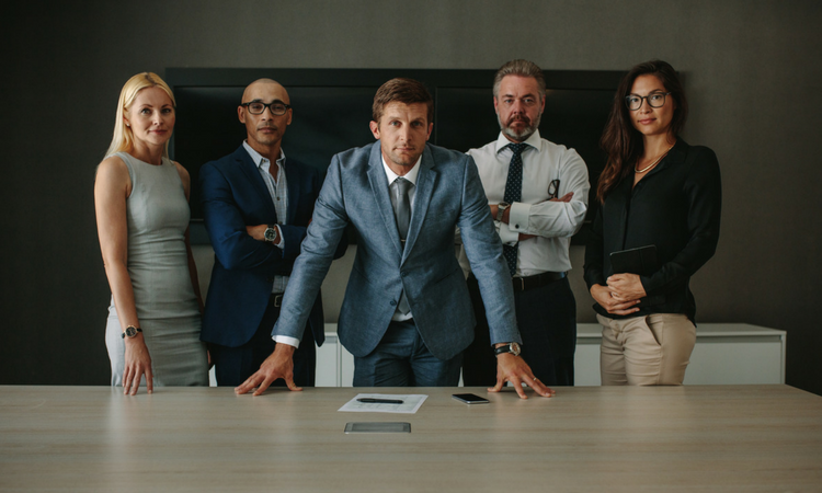corporate group of 5 standing in front of conference table, looking straight ahead at you