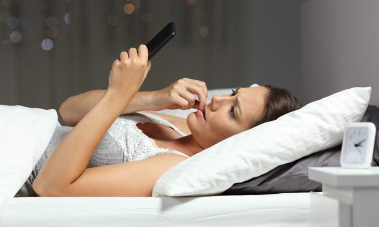 woman reading phone intently in bed